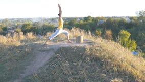 Giovane uomo sportivo che sta alla posa di yoga all'aperto L'yoga di pratica del tipo caucasico si muove e posiziona in natura Be Fotografie Stock