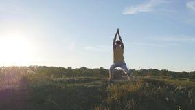 Giovane uomo sportivo che sta alla posa di yoga all'aperto L'yoga di pratica del tipo caucasico si muove e posiziona in natura at Fotografia Stock Libera da Diritti