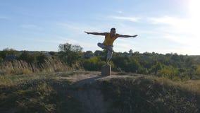 Giovane uomo sportivo che sta alla posa di yoga all'aperto L'yoga di pratica del tipo caucasico si muove e posiziona in natura yo Fotografie Stock Libere da Diritti