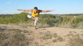 Giovane uomo sportivo che sta alla posa di yoga dell'albero all'aperto L'yoga di pratica del tipo caucasico si muove e posiziona  Fotografia Stock