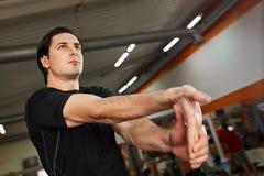 Giovane uomo sportivo nello sportwear nero che allunga braccio prima dell'allenamento della palestra Immagine Stock