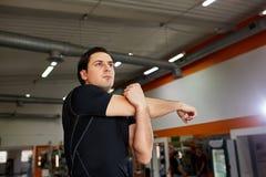 Giovane uomo sportivo nello sportwear nero che allunga braccio prima dell'allenamento della palestra Fotografia Stock