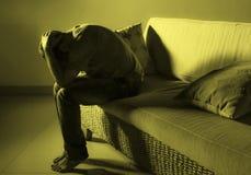 Giovane uomo triste e frustrato disperato che si addolora a casa problema di depressione dello strato del sofà e gridare di soffe immagine stock libera da diritti