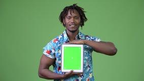 Giovane uomo turistico africano bello che mostra compressa digitale archivi video