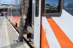 Giovane uomo turistico sulle porte vicine del treno della stazione ferroviaria Immagine Stock Libera da Diritti