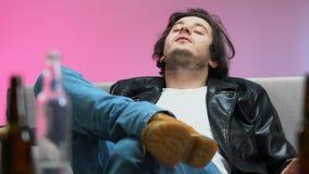 Giovane uomo ubriaco che si trova sullo strato, ritmo ritenente di musica, partito domestico, vita in ozio video d archivio