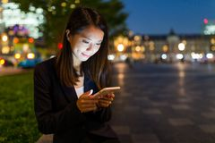Giovane uso della donna di affari del cellulare nella città di Tokyo Immagine Stock