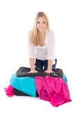 Giovane valigia attraente dell'imballaggio della donna isolata su bianco Fotografie Stock Libere da Diritti
