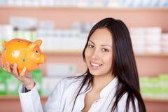 Giovane venditora nel porcellino salvadanaio della tenuta della farmacia Fotografie Stock