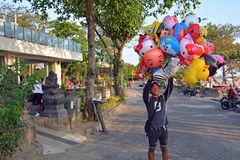 Giovane venditore dei palloni a forma di dell'animale alla spiaggia di Legian Fotografia Stock Libera da Diritti