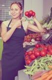 Giovane venditore femminile amichevole che tiene i pomodori maturi freschi sul segno Fotografia Stock Libera da Diritti
