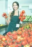 Giovane venditore femminile che tiene i pomodori maturi freschi Fotografie Stock Libere da Diritti