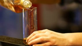Giovane versamento del barista scozzese nella tazza misurabile Sta preparando un cocktail dell'alcool video d archivio
