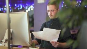 Giovane in vetri che gettano sulle carte che si siedono davanti al nuovo computer in ufficio moderno L'impiegato di concetto ha p video d archivio
