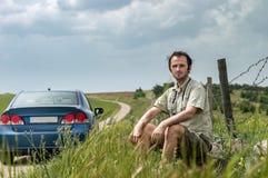 Giovane viaggiatore che si siede vicino alla sua automobile blu in campagna fotografia stock libera da diritti