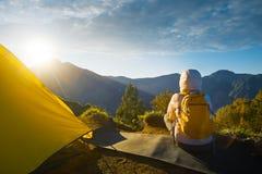 Giovane viaggiatore con il viaggiatore con zaino e sacco a pelo che gode della vista di alba alla sommità t Fotografia Stock Libera da Diritti