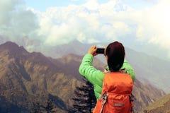 Giovane viaggiatore con zaino e sacco a pelo asiatico della donna che prende foto con lo smartphone Fotografie Stock