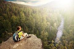 Giovane viaggiatore con zaino e sacco a pelo che esamina la distanza dal picco di montagna immagini stock