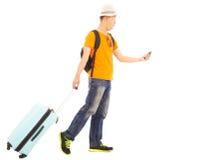 Giovane viaggiatore con zaino e sacco a pelo che porta un bagaglio e che tiene uno smartphone Fotografia Stock Libera da Diritti
