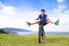 Giovane viaggiatore con zaino e sacco a pelo divertente che guida una bicicletta su un prato Immagini Stock Libere da Diritti