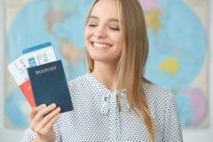 Giovane viaggiatore femminile biondo in un primo piano dei passaporti della tenuta dell'agenzia di giro Immagini Stock Libere da Diritti