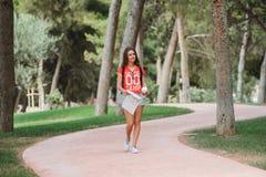 Giovane viaggiatore femminile sportivo con il sorriso sveglio che studia una mappa in parco Immagine Stock