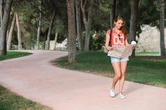 Giovane viaggiatore femminile sportivo con il sorriso sveglio che studia una mappa in parco Immagini Stock