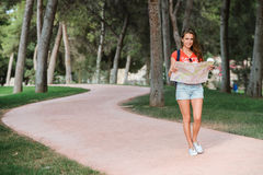 Giovane viaggiatore femminile sportivo con il sorriso sveglio che studia una mappa in parco Immagini Stock Libere da Diritti