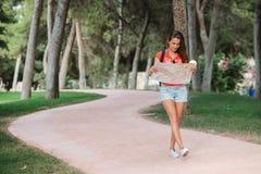 Giovane viaggiatore femminile sportivo con il sorriso sveglio che studia una mappa in parco Fotografia Stock