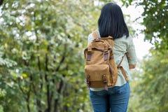Giovane viaggio felice di viaggiatore con zaino e sacco a pelo della donna del viaggiatore in FO naturali verdi fotografia stock