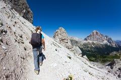 Giovane viandante che cammina su una traccia di montagna. Immagine Stock
