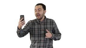 Giovane video della registrazione di blogger sul suo telefono mentre camminando sul fondo bianco stock footage