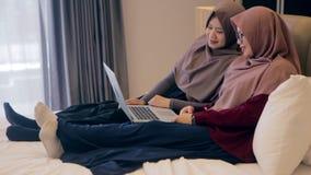 Giovane video musulmano dell'orologio della donna due sul computer portatile nella camera da letto archivi video