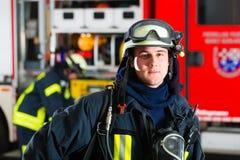 Giovane vigile del fuoco in uniforme davanti al firetruck Fotografie Stock Libere da Diritti