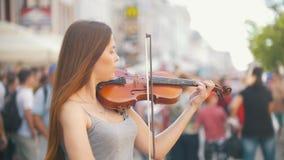 Giovane violinista femminile che gioca le fiddle sulla via pedonale al giorno di estate stock footage