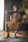 Giovane violoncellista che gioca seriamente violoncello fotografia stock libera da diritti