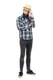 Giovane visiera seria del cappello di paglia della tenuta dei pantaloni a vita bassa che esamina macchina fotografica fotografie stock