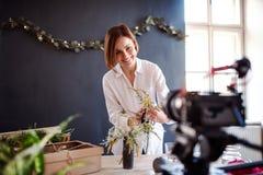 Giovane vlogger creativo della donna in un negozio di fiore Una partenza dell'affare del fiorista fotografia stock libera da diritti