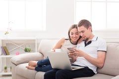 Giovane web delle coppie che pratica il surfing sul computer portatile, spazio della copia fotografia stock libera da diritti