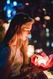 Giovane womant con le lanterne cinesi che galleggiano nel lago fotografia stock