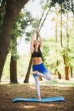 Giovane yoga dei professionisti della donna di yoga sulla natura fiore della sfuocatura della priorità bassa all'interno come gli Fotografia Stock