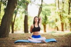 Giovane yoga dei professionisti della donna di yoga sulla natura fiore della sfuocatura della priorità bassa all'interno come gli Immagine Stock