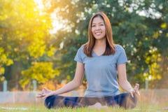 Giovane yoga di pratica sorridente asiatica della donna, sedentesi nella posa facile Fotografia Stock