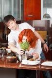 Giovani accoppiamenti sulla cucina: portile i fiori Immagine Stock Libera da Diritti
