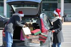Giovani acquisti di Natale di caricamento delle coppie nel tronco di automobile su parcheggio del centro commerciale fotografie stock
