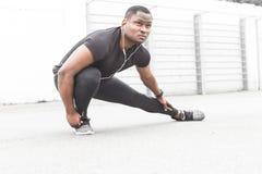 Giovani addestramento dell'atleta del pareggiatore e fare allenamento maschii all'aperto nella città un uomo di colore che riposa immagini stock