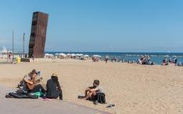 Giovani adulti che giocano musica sulla spiaggia di Barcellona Fotografia Stock Libera da Diritti