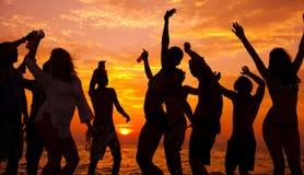 Giovani adulti che godono di un partito tropicale della spiaggia Fotografia Stock