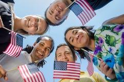 Giovani adulti patriottici con le bandiere Immagine Stock