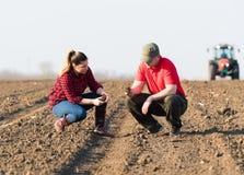 Giovani agricoltori che examing sporcizia mentre il trattore sta arando i campi Fotografia Stock Libera da Diritti